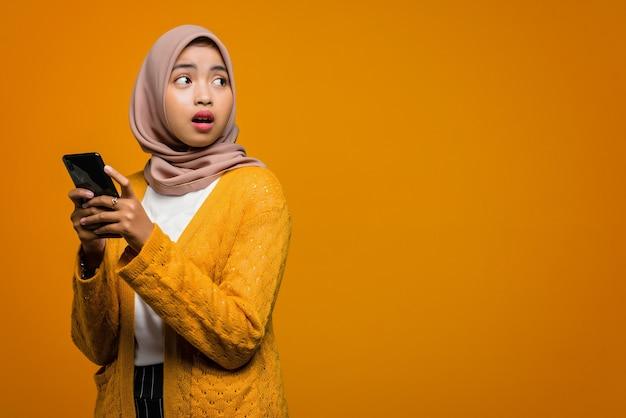 Chocado com a bela mulher asiática segurando um smartphone com um espaço vazio