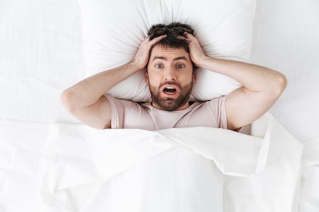 Chocado confuso jovem bonito de manhã debaixo do cobertor na cama