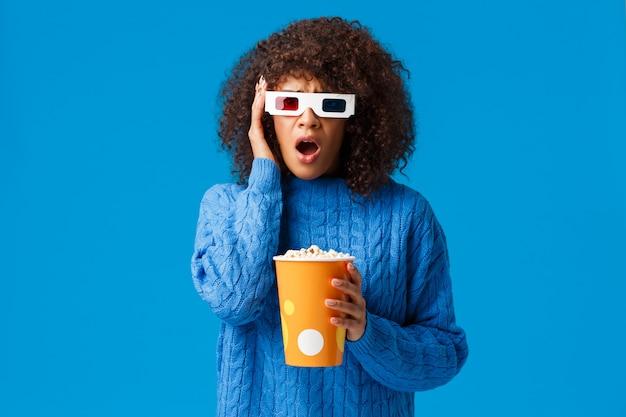 Chocado e chateado, preocupada jovem afro-americana simpatizante personagem principal no filme assistindo filme em óculos 3d, assistir cinema comendo pipoca, ofegando e agarre a cabeça em causa