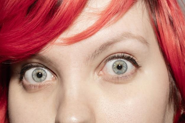 Chocado. feche o rosto de uma bela jovem caucasiana, concentre-se nos olhos.