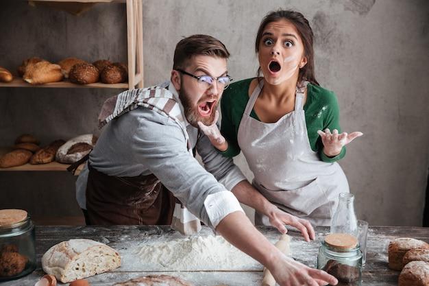 Chocado homem e mulher em pé perto da mesa com farinha