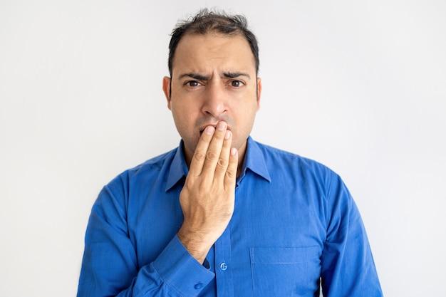Chocado homem indiano cobrindo a boca com a mão