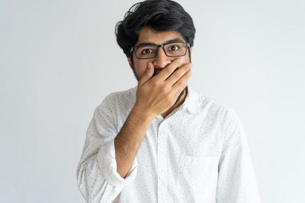 Chocado homem indiano emocional cobrindo a boca em emoção.