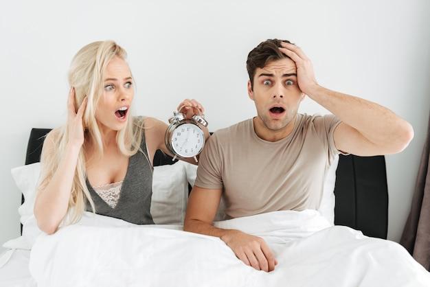 Chocado jovem casal sentado na cama com a boca aberta e segurando o relógio despertador