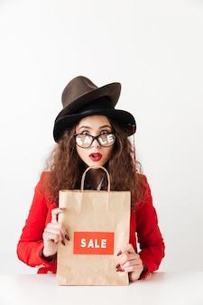 Chocado jovem caucasiana segurando sacola de compras