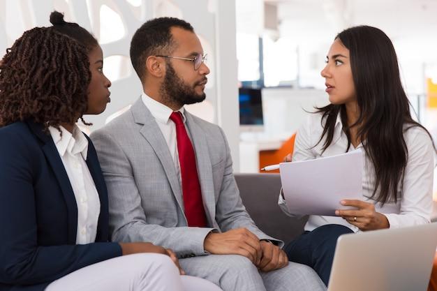 Chocado jovem funcionária pedindo colegas para ajudar