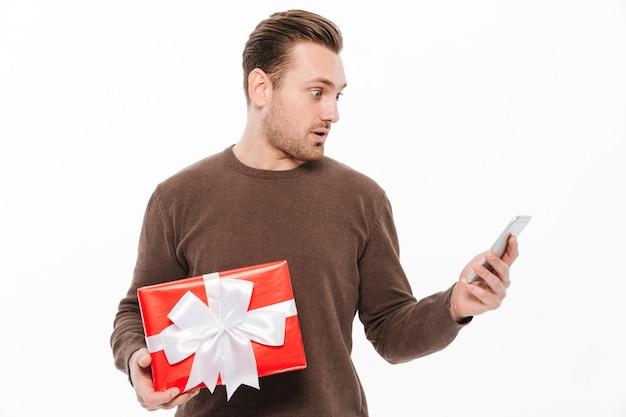 Chocado jovem segurando surpresa de caixa de presente