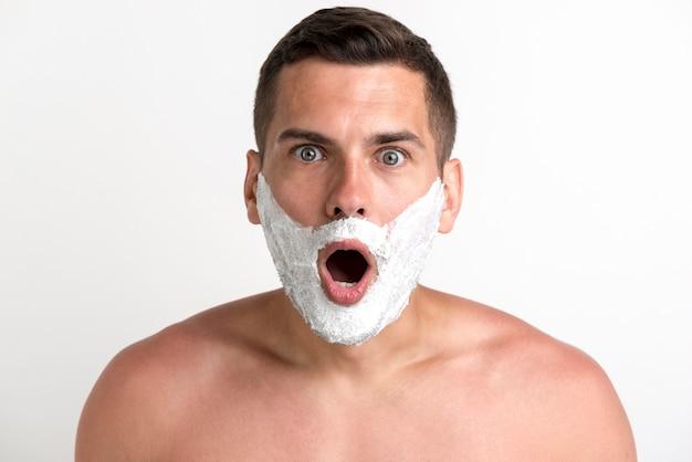 Chocado jovem sem camisa aplicou creme de barbear, olhando para a câmera