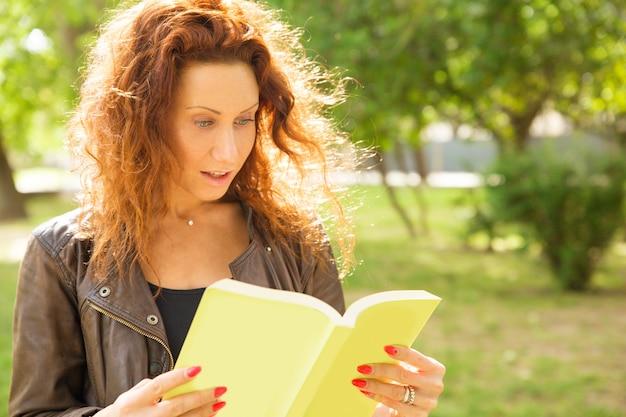 Chocado mulher excitada em pé no parque, lendo o livro
