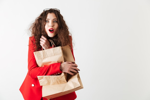 Chocado mulher segurando sacolas de papel