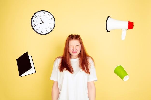 Chocado, prazo. retrato de mulher jovem caucasiana em fundo amarelo do estúdio, muitas tarefas. como gerenciar o tempo certo. conceito de trabalho, negócios, finanças, freelance, autogestão, planejamento.