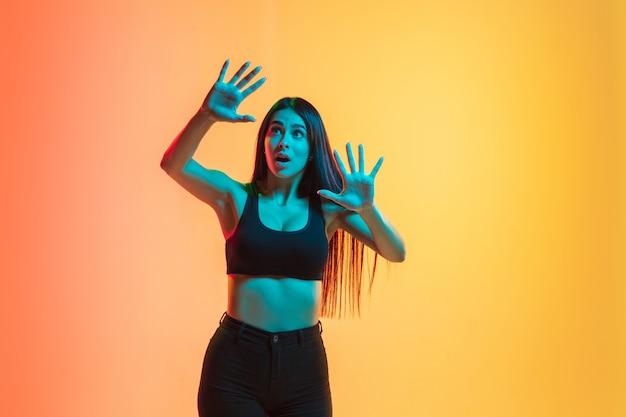 Chocado. retrato de jovem mulher caucasiana em fundo gradiente estúdio amarelo-laranja em luz de néon. conceito de juventude, emoções humanas, expressão facial, vendas, anúncio. modelo morena de ajuste desportivo.
