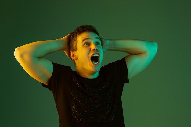 Chocado, segurando a cabeça nas mãos. retrato do homem caucasiano isolado no fundo verde do estúdio em luz de néon.