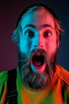 Chocado, surpreso, de perto. retrato do homem caucasiano em fundo gradiente de estúdio em luz de néon. lindo modelo masculino com estilo hippie. conceito de emoções humanas, expressão facial, vendas, anúncio.