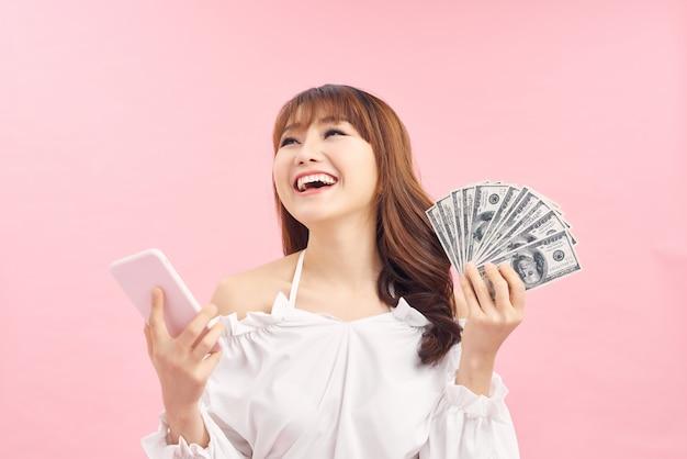 Chocado surpreso gritando jovem bonita mulher posando isolado sobre o fundo da parede rosa, usando telefone móvel segurando dinheiro.
