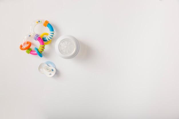 Chocalho; chupeta e garrafa de leite, isolada no fundo branco