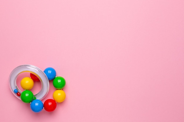 Chocalho infantil colorido sobre fundo rosa, vista superior do brinquedo para crianças e bebês com copyspace