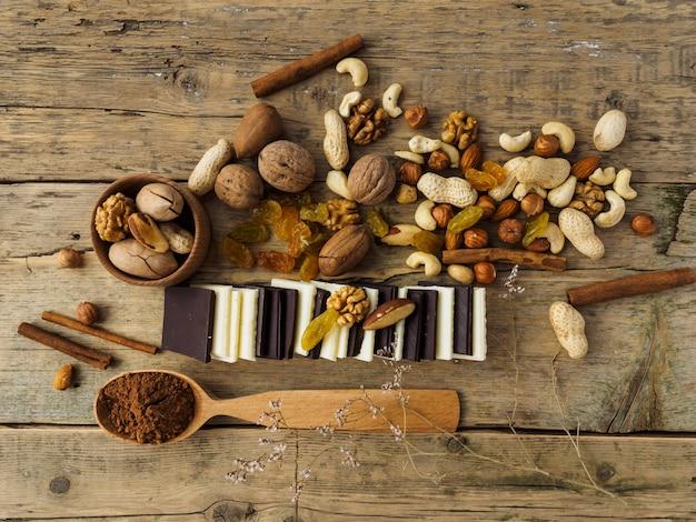Chocolate amargo e ao leite, nozes e outros doces em uma mesa de madeira.