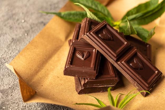 Chocolate amargo vegan com folhas de cannabis. deserto com manteiga de cbd. maconha medicinal em alimentos, vegan, conceito de suplementos