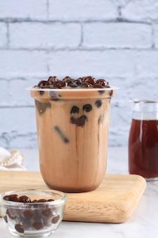 Chocolate ao leite com gelo de taiwan ou café com pérolas de tapioca boba no topo com folha de hortelã como enfeite. na tabela de madeira. bebida de chocolate boba