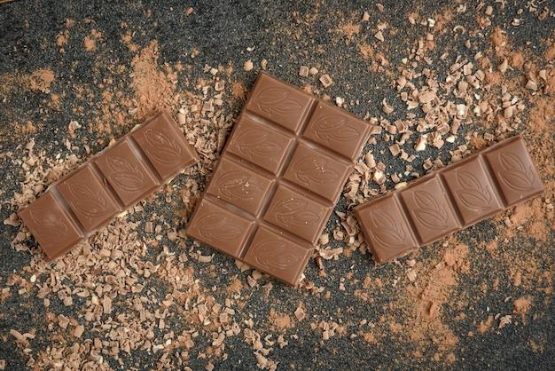 Chocolate ao leite em barra de chocolate e cacau na superfície preta