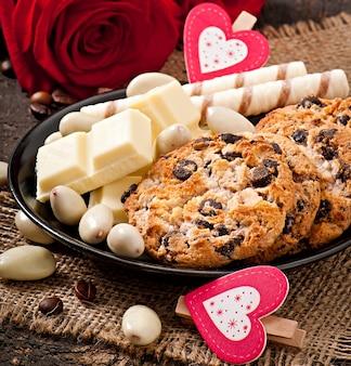 Chocolate branco, amêndoas e biscoitos numa superfície de madeira