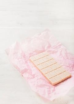 Chocolate branco em papel rosa contra o pano de fundo texturizado