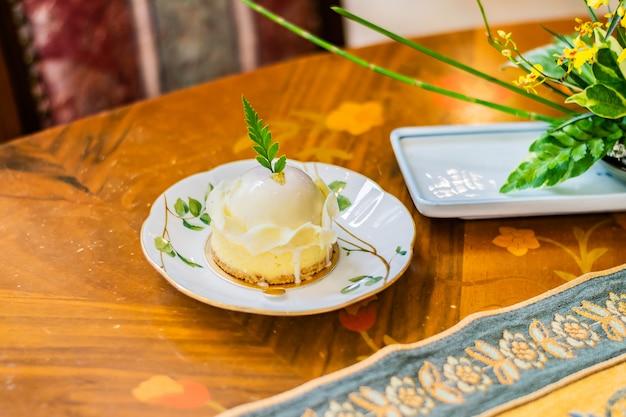 Chocolate branco sortido com bolo de bagas, servido em um prato branco sobre a toalha de mesa de luxo e a mesa de madeira