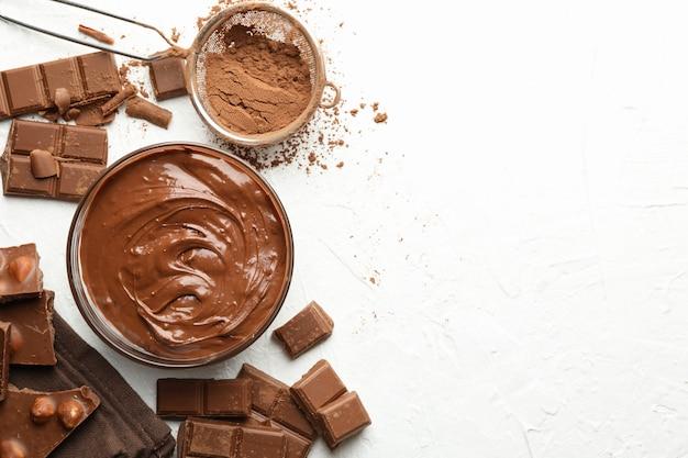 Chocolate, chocolate derretido e pó no fundo branco