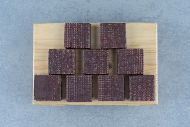 Chocolate coberto em barra de wafer crocante no quadro, sobre a mesa de mármore.