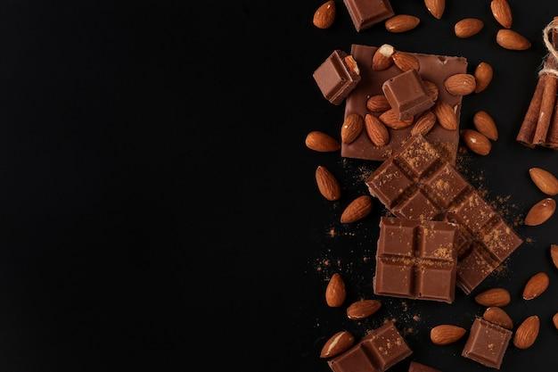 Chocolate com amêndoas e canela em close-up de fundo escuro, espaço de cópia