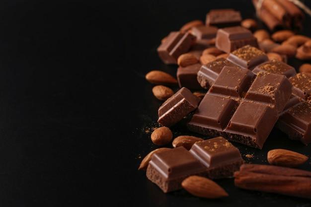 Chocolate com amêndoas e canela em close-up de mesa escura, foco seletivo