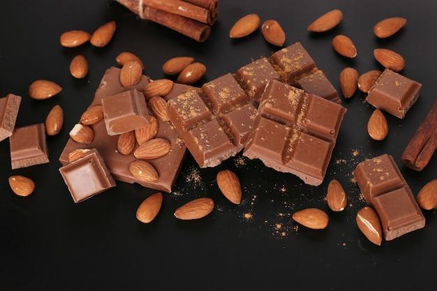 Chocolate com amêndoas e canela em uma superfície escura close-up
