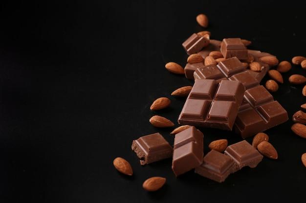 Chocolate com amêndoas em uma superfície escura, foco seletivo, cópia espaço