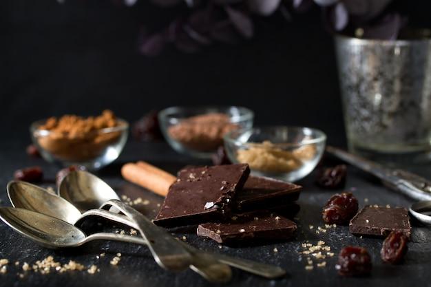 Chocolate com colheres, cacau e açúcar no escuro