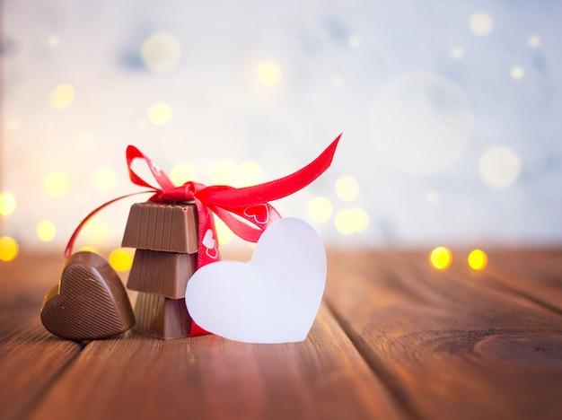 Chocolate com fita e coração no dia de são valentim e bokeh.