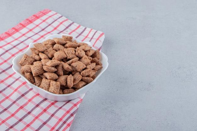 Chocolate com flocos de milho em uma tigela branca sobre uma superfície de pedra