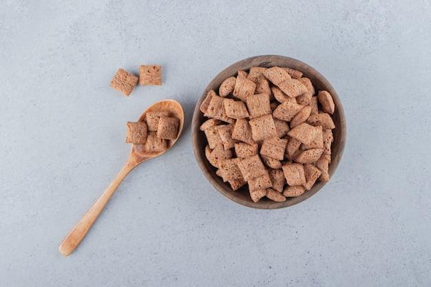 Chocolate com flocos de milho em uma tigela de madeira sobre uma superfície de pedra