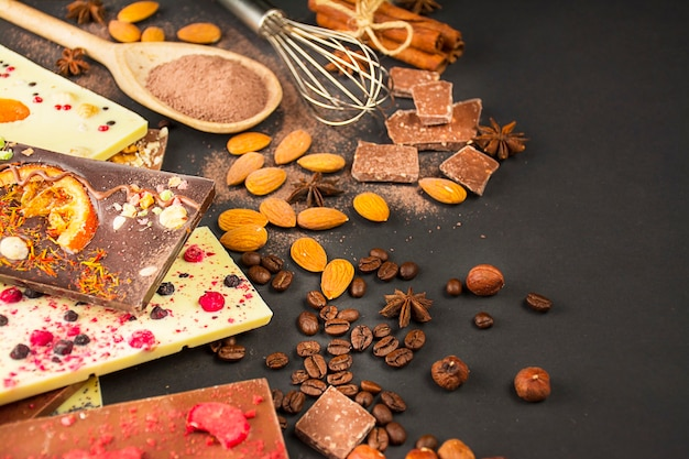 Chocolate com frutas vermelhas, nozes, frutas secas em um fundo escuro. vários tipos de chocolate preto e branco. barra de chocolate. bandeira. fundo de chocolate. copie o espaço.
