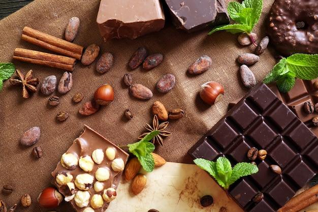 Chocolate com hortelã, especiarias e grãos de café na mesa, closeup