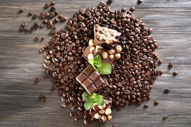 Chocolate com menta e grãos de café na mesa de madeira