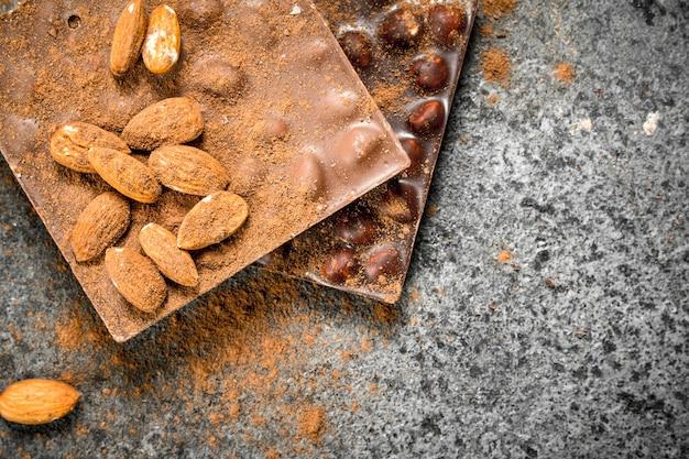 Chocolate com nozes e cacau em pó na mesa rústica.