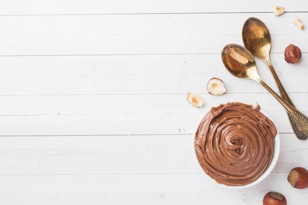 Chocolate da porca do nougat em uma placa em um fundo branco com porcas da avelã.