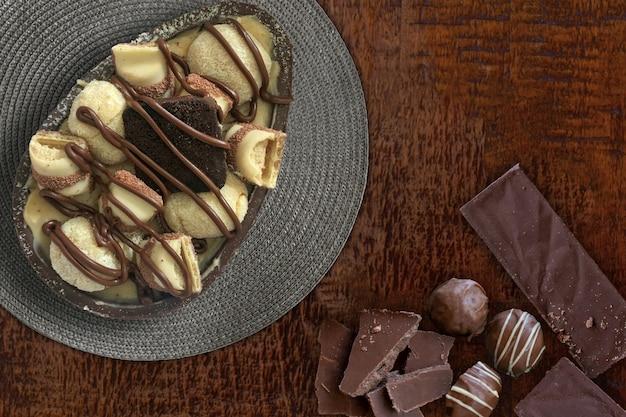 Chocolate de ovo de páscoa, chocolates e trufas na mesa de madeira