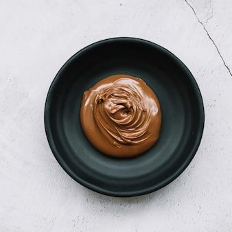 Chocolate derretido em tigela preta sobre o pano de fundo branco