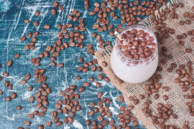 Chocolate e grãos de café com uma xícara de bebida em azul.