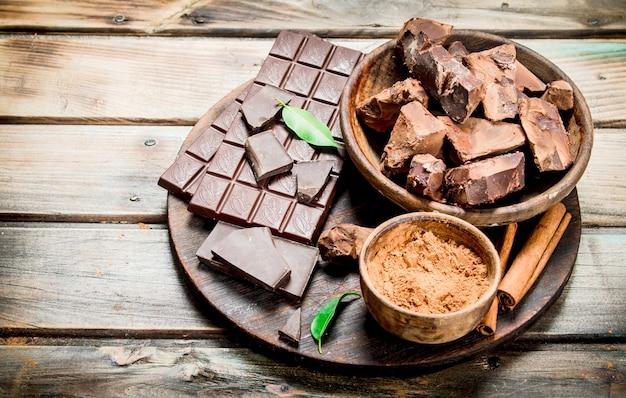 Chocolate em uma tigela com cacau em pó na placa. em uma mesa de madeira.