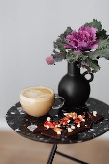 Chocolate escuro frágil e chá de leite sobre uma mesa preta com uma flor de couve ornamental