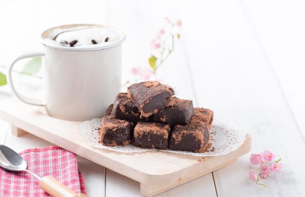 Chocolate nama na placa de madeira fundo de madeira branca