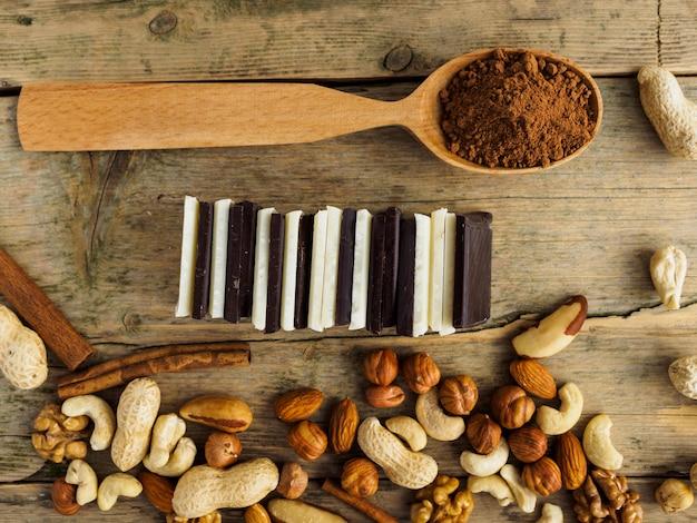 Chocolate, nozes, passas e colher de cacau na superfície de madeira.